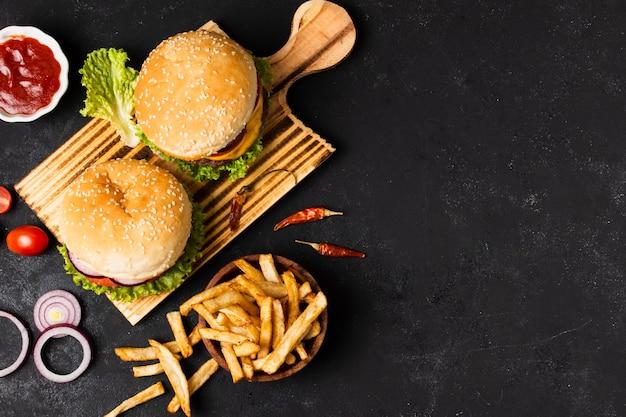 Плоская кладка гамбургеров и картофеля фри с копией пространства Premium Фотографии