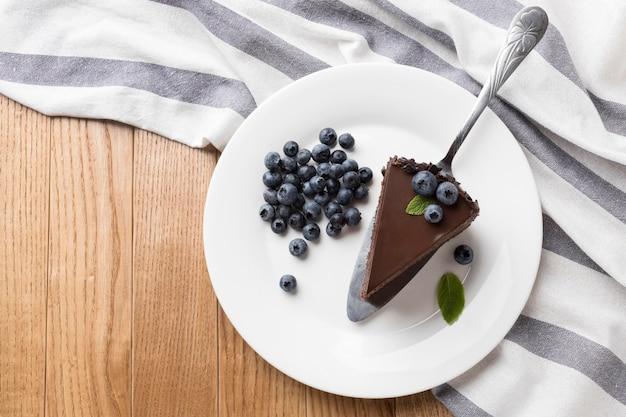 Плоский кусок шоколадного торта на тарелке с черникой Premium Фотографии