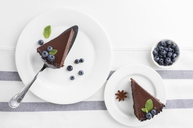Плоская кладка кусочков шоколадного торта на тарелки с черникой Бесплатные Фотографии