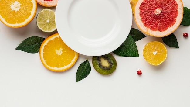 葉とプレートと柑橘類のフラットレイ 無料写真