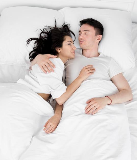 一緒にベッドで寝ているカップルのフラットレイアウト 無料写真