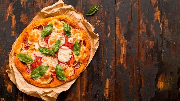 木製のテーブルにおいしいピザのコンセプトのフラットレイアウト 無料写真