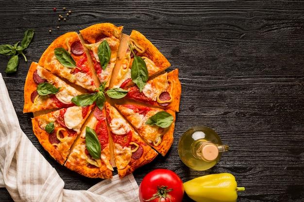 木製のテーブルにおいしいピザのコンセプトのフラットレイアウト Premium写真