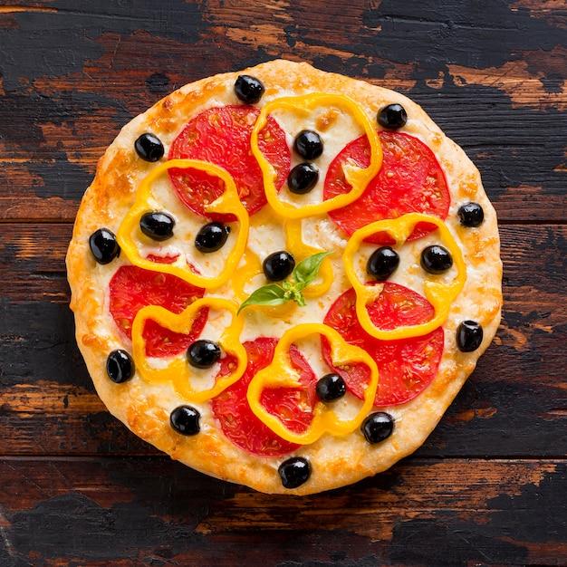 木製のテーブルにおいしいピザのフラットレイアウト 無料写真