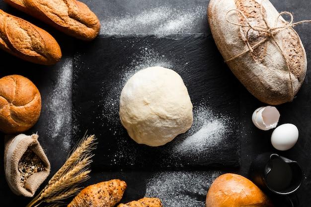 生地と黒の背景にパンのフラットレイアウト 無料写真