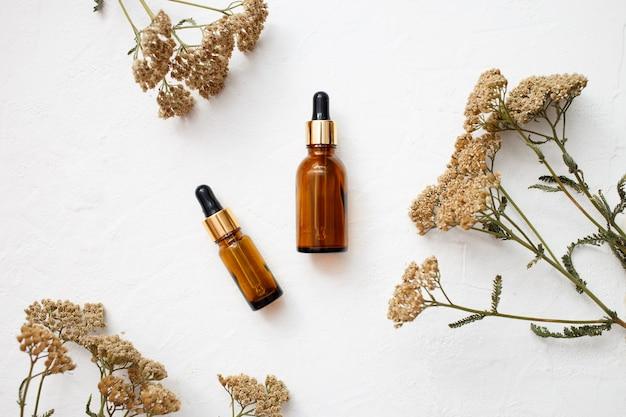 Плоская планировка продуктов эфирного масла для ухода за кожей в стеклянной бутылке для макета в минималистичном стиле на белом фоне. Premium Фотографии
