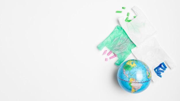 Плоская планировка земного шара с полиэтиленовыми пакетами и копией пространства Бесплатные Фотографии