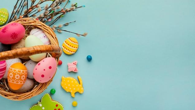 Плоская кладка пасхальных яиц в корзине с фигурами кролика и бабочки Бесплатные Фотографии