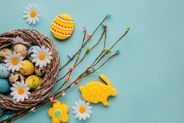 Плоская кладка пасхальных яиц в корзине с цветами ромашки Бесплатные Фотографии