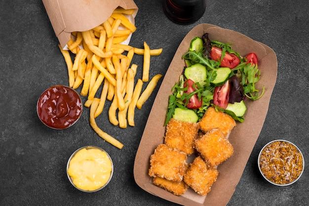 フラットフライドチキンナゲットのサラダとフライドポテト 無料写真