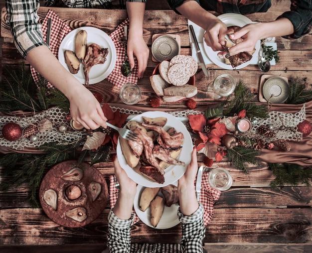 一緒に食べたり飲んだりする友人の手のフラットレイアウト。パーティー、集まり、素朴な木製のテーブルで一緒に祝う人々のトップビュー 無料写真