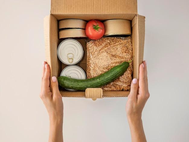 Плоская планировка руки, держащей коробку для пожертвований еды Бесплатные Фотографии