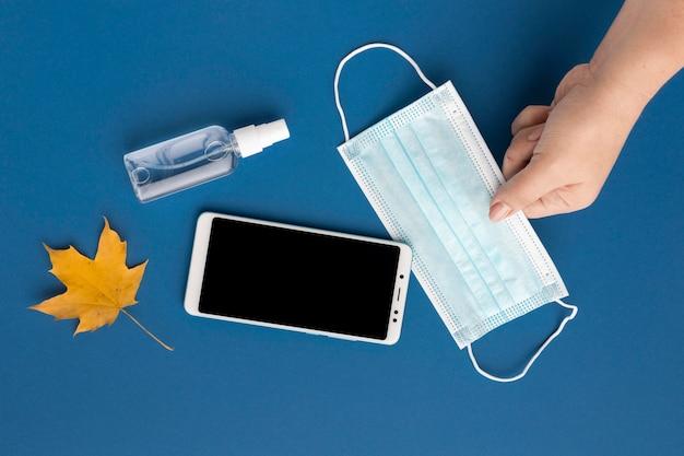 Плоское положение руки, держащей медицинскую маску со смартфоном и осенним листом Бесплатные Фотографии