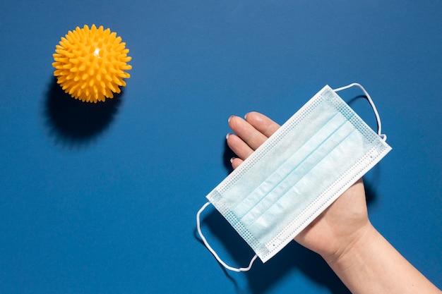 Плоская форма руки, держащей медицинскую маску с вирусом Бесплатные Фотографии