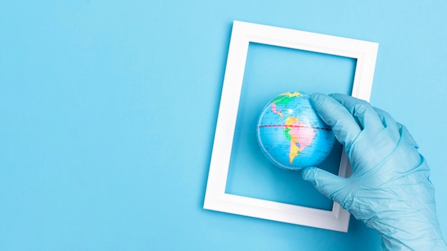 Плоская ладонь с хирургической перчаткой, держащей земной шар в рамке Бесплатные Фотографии