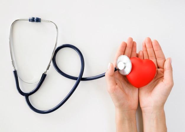 聴診器でハートの形を保持している手のフラットレイアウト 無料写真