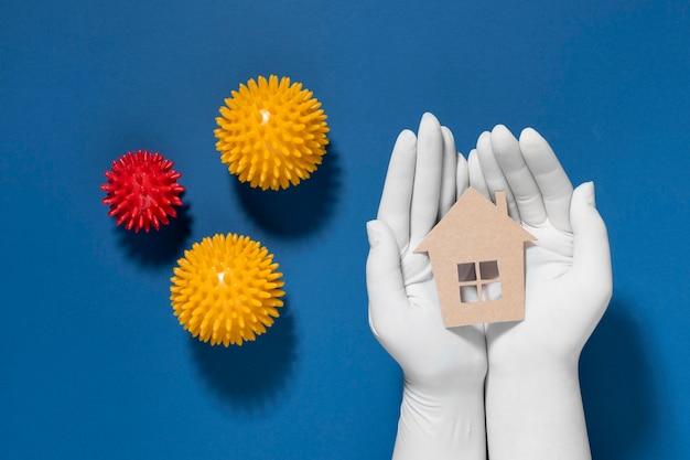 Плоское положение рук в перчатках, удерживающих и защищающих дом от вирусов Бесплатные Фотографии