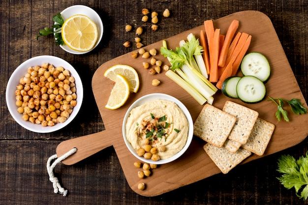 Плоская кладка хумуса с ассортиментом овощей Бесплатные Фотографии