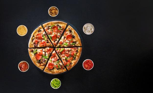 暗い表面の上面にイタリアのピザと周りの新鮮な食材のフラットレイアウト Premium写真