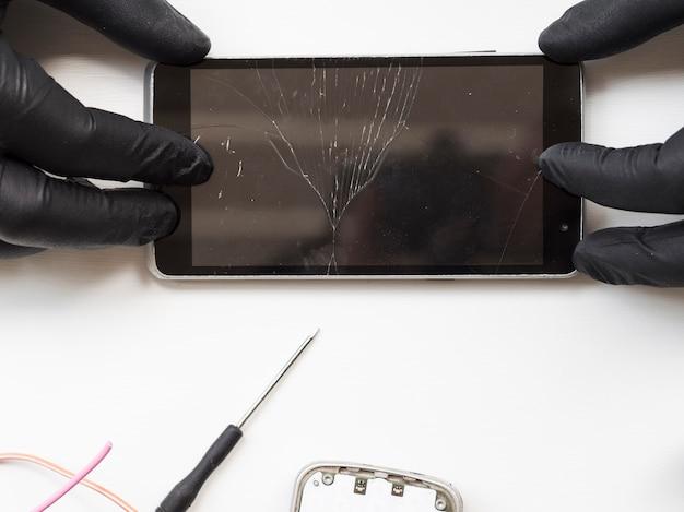 Плоский мужчина держит сломанный телефон Premium Фотографии