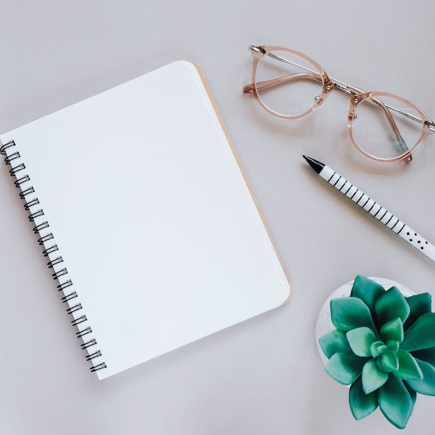 Flat lay of minimal workspace desk with notebook, eyeglasses and green plant, copy space Free Photo