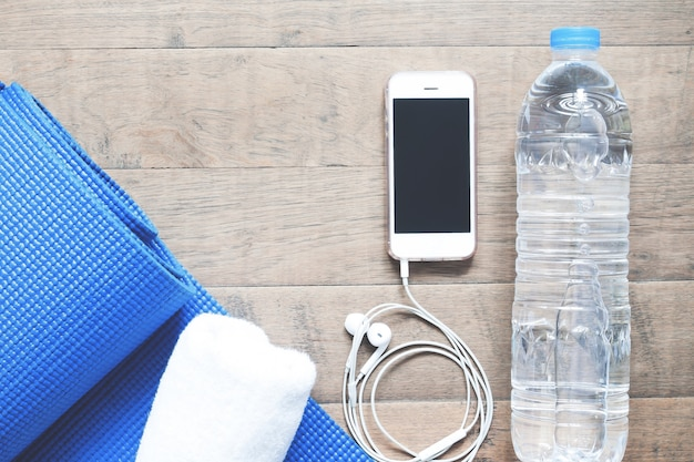 Flat Lay Of Mobile Phone With Earphones Water Bottle Towel And Blue Yoga Mat