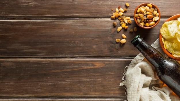 ビール瓶とチップスとナッツのフラットレイ 無料写真