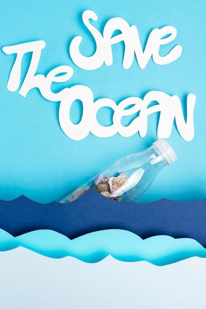 プラスチック製のボトルで紙の海の波を平らに置き、海を救う 無料写真