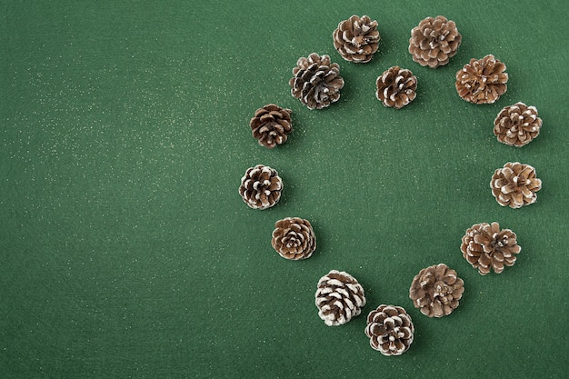 緑の表面に松ぼっくりのクリスマスデコレーションのフラットレイ 無料写真