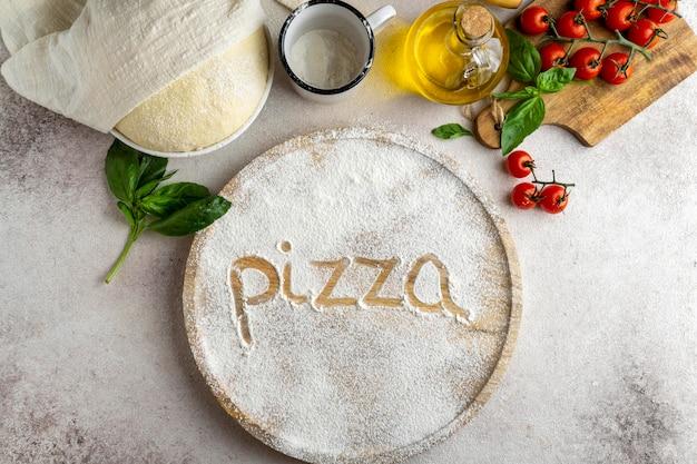 Плоская кладка теста для пиццы с деревянной доской и словом, написанным в муке Бесплатные Фотографии