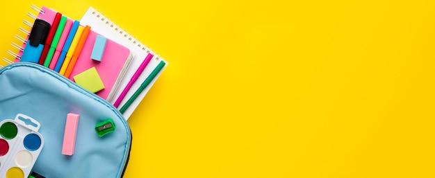Плоская планировка школьных принадлежностей с карандашами в рюкзаке и копией пространства Бесплатные Фотографии
