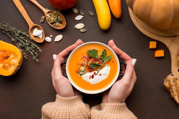 Плоский суп из тыквы в миске, держась за руки Бесплатные Фотографии