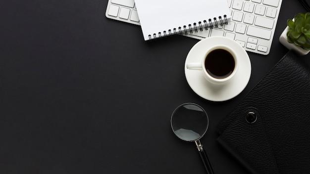 Плоский рабочий стол с кофейной чашкой и увеличительным стеклом Premium Фотографии