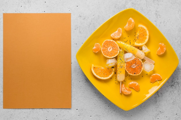 オレンジとコピースペースのプレートにおいしいアイスキャンディーのフラットレイ 無料写真