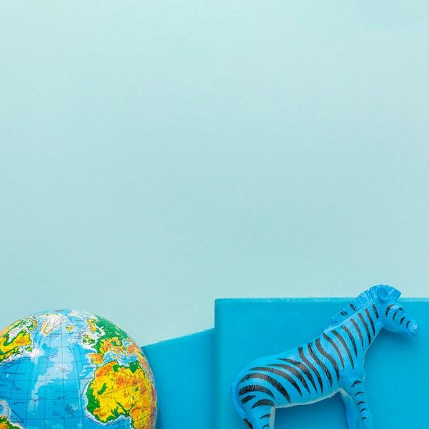 Плоская планировка фигурки зебры с планетой земля и книгами на день животных Бесплатные Фотографии