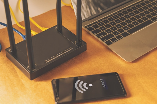 Flat lay office table with wifi router, computer and supplies top view Premium Photo