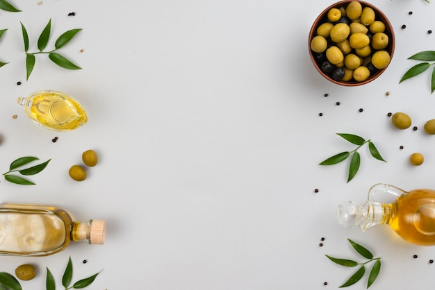 Flat lay olives, leaves and olive oil Premium Photo
