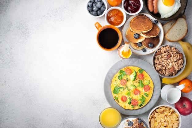 Flat lay of omelette and pancakes for breakfast with cereal and jam Free Photo