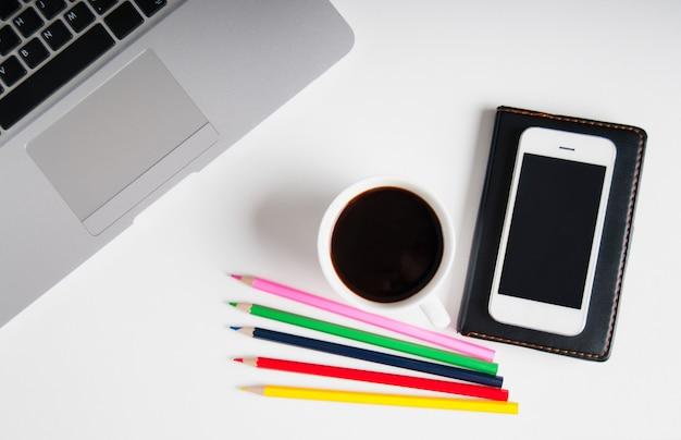 フラットは、ラップトップコンピューター、携帯電話のガジェット、消耗品、ブラックコーヒーと白い木製のワークスペースに横たわっていた。 Premium写真