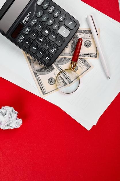 Плоская планировка или вид сверху калькулятора, долларовых денег и белого блокнота на красном фоне, бизнес, финансы, сбережения, инвестиции, налоги или концепция бухгалтерского учета Premium Фотографии