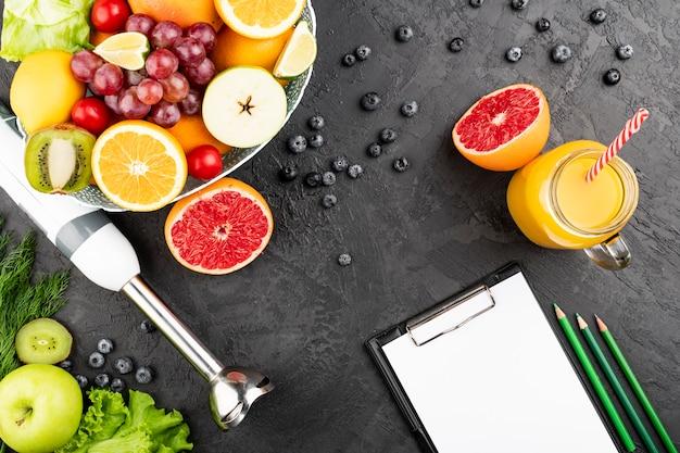 Flat lay orange juice and bowl of fruit Free Photo