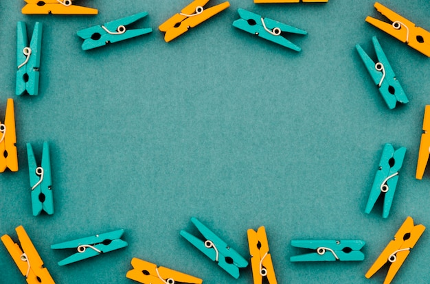 Flat-lay orange and turquoise clothes pins frame Free Photo