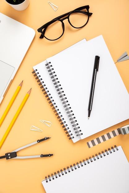 Flat lay organised arrangement of desk elements on orange background Free Photo