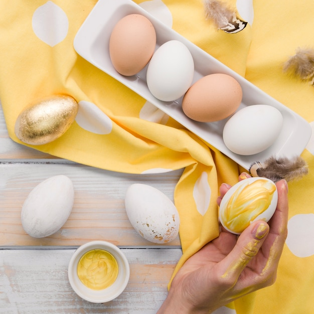 Flat lay of painted egg for easter held by hand Free Photo