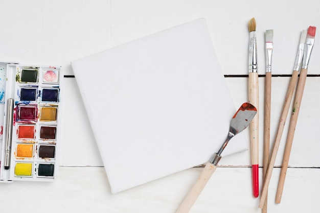 Flat lay of painting essentials with brushes and palette Premium Photo