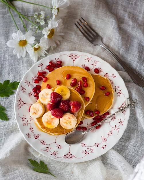 Flat lay pancake tower with banana and raspberries Free Photo