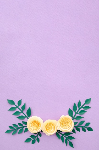 Flat lay paper flowers and leaves on purple background Free Photo