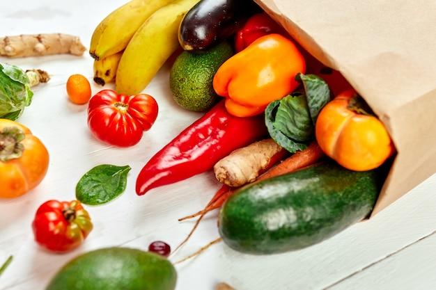 新鮮な野菜や果物の品揃え、バイオヘルシー、白い壁に有機食品、スーパーマーケットスタイル、食料品、ダイエット野菜食品が入った平置きの紙の買い物袋。 Premium写真
