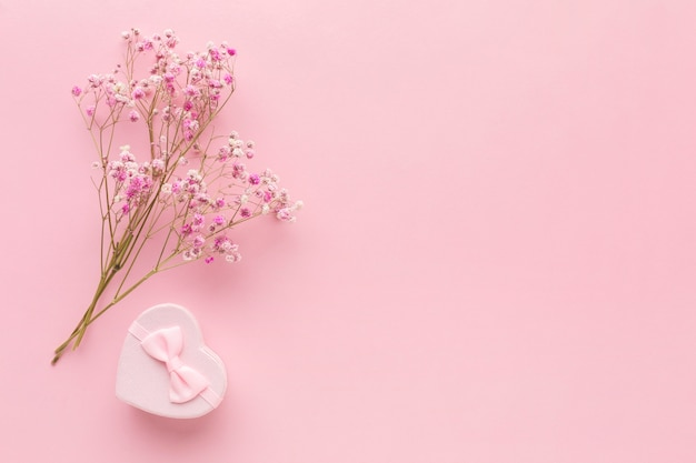 Flat lay of pink gift with flowers and copy space Free Photo