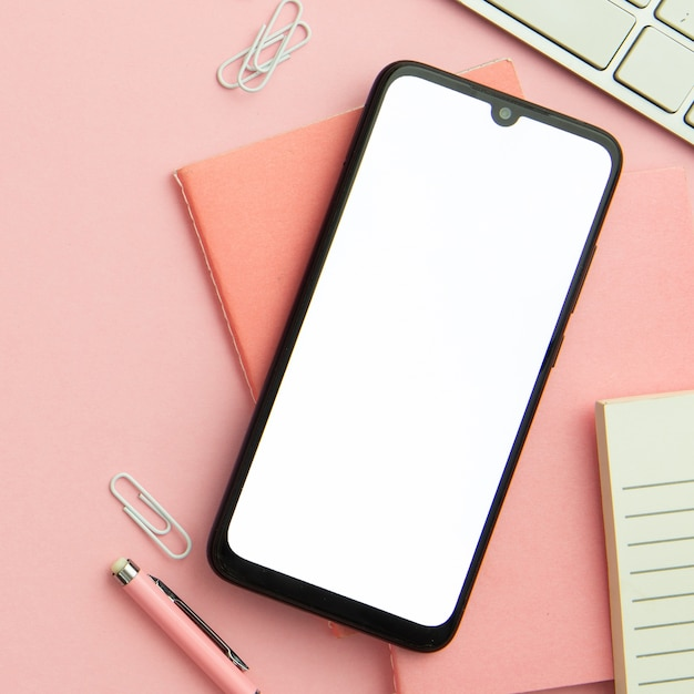 Flat lay pink workplace arrangement with empty phone close-up Free Photo